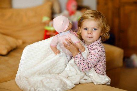 Foto de Adorable niño niña linda jugando con muñeca. Bebé sano feliz jugar del niño que se divierte con el juego de rol, madre en el hogar o guardería. Hija activa con juguete - Imagen libre de derechos