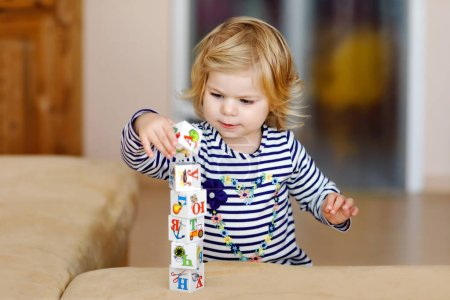 Photo for Adorable toddler girl playing with educational toys in nursery. Happy healthy child having fun with colorful different plastic blocks at home. Cute baby learning creating and building. - Royalty Free Image