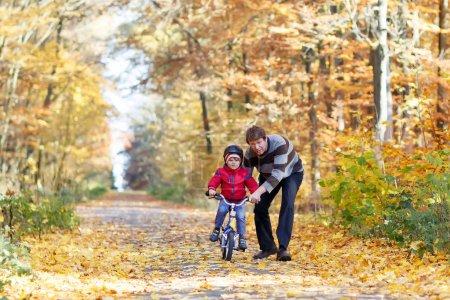 Photo pour Petit garçon et son père dans le parc d'automne avec un vélo. Papa enseigne le vélo à son fils. Loisirs familiaux actifs. Enfant avec casque à vélo. Concept sécurité, sport, loisirs avec enfants . - image libre de droit