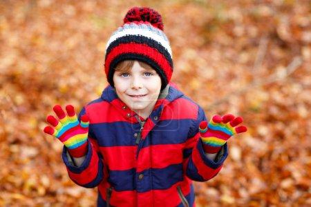 Mignon petit garçon sur fond de feuilles d'automne dans le parc.