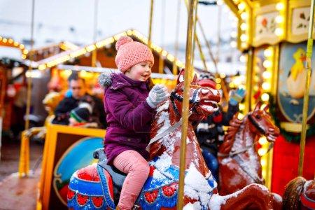 Adorable petite fille qui monte sur un cheval de carrousel à la fête foraine ou au marché de Noël, en plein air .
