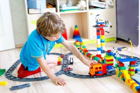 Photo pour Garçon adorable petit blond enfant jouer avec des blocs en plastique colorés et la création de la gare. Enfants s'amuser à fabriquer des jouets de chemin de fer à la maison. - image libre de droit