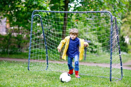 Photo for Active cute little kid boy playing soccer and football and having fun, outdoors. Child having game on rainy day. Wearing yellow rain coat and red rubber boots - Royalty Free Image