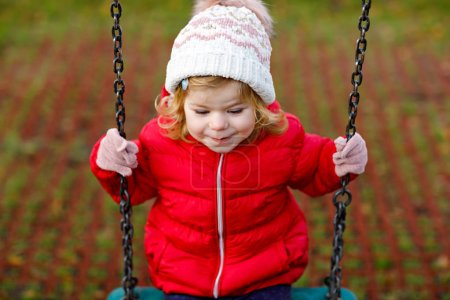 Photo for Cute toddler girl having fun on playground. Happy healthy little child climbing, swinging and sliding on different equipment. On cold day in colorful clothes. Active outdoors game for children. - Royalty Free Image