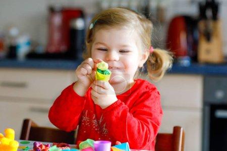 Photo pour Adorable petit bambin fille mignonne avec de l'argile coloré. Santé bébé enfant jouant et en créant des jouets de pâte à modeler. Petit gamin glaise à modeler de moulage et de l'apprentissage. - image libre de droit