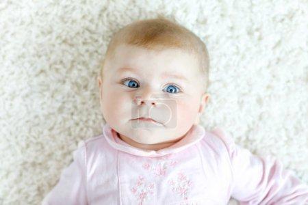 Photo pour Gros plan d'une petite fille de deux ou trois mois aux yeux bleus. Enfant nouveau-né, petite fille adorable souriante et attentive regardant surpris par la caméra. Famille, nouvelle vie, concept d'enfance - image libre de droit