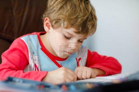 Photo pour Portrait d'école heureux mignon enfant garçon à la maison faire des devoirs. Petit enfant, écrit avec des crayons colorés, à l'intérieur. École élémentaire et l'éducation. Apprentissage enfant écrivant des lettres et des chiffres. - image libre de droit