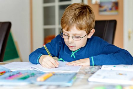 Photo for Portrait of cute school kid boy wearing glasses at home making homework. Little concentrated child writing with colorful pencils, indoors. Elementary school and education. - Royalty Free Image