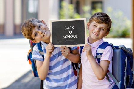 Photo pour Deux petits garçons avec sac à dos ou sacoche. Des écoliers en route pour l'école. Enfants en bonne santé, frères et meilleurs amis à l'extérieur dans la rue. Retourner à l'école à la craie. Heureux frères et sœurs . - image libre de droit