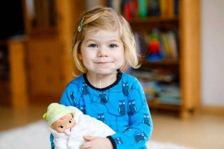 Photo pour Adorable petite fille mignonne tout-petit jouant avec poupée. Bébé enfant heureux et en bonne santé s'amuser avec un jeu de rôle, jouer à la mère à la maison ou à la crèche. Fille active avec jouet - image libre de droit