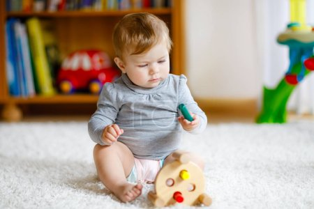 Photo for Adorable baby girl playing with educational toys . Happy healthy child having fun with colorful different wooden toy at home. Early development for children with nature toy - Royalty Free Image