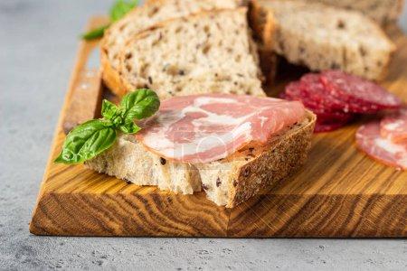 Photo pour Pain artisanal traditionnel aux graines, saucisse de porc et salami servi sur une planche à découper en bois. Sandwich ouvert avec saucisse de porc . - image libre de droit