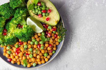 Photo for Healthy vegetable lunch of broccoli, roasted chickpeas, avocado, green peas, pomegranate seeds, lime and mint on a ceramic plate. Vegan food, clean eating or dieting concept. - Royalty Free Image