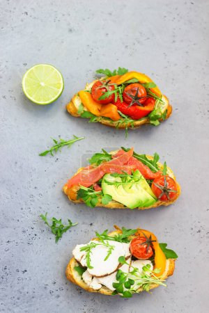 Photo for Variety of croissant sandwiches with grilled pepper, tomatoes, smoked salmon, turkey, avocado and arugula served with micro green on grey concrete background. - Royalty Free Image