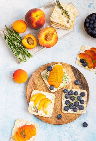 Photo for Mini rice cakes with blueberries, apricots, nectarines and cream cheese with honey for healthy breakfast. Light blue background. Summer dieting sandwiches. - Royalty Free Image
