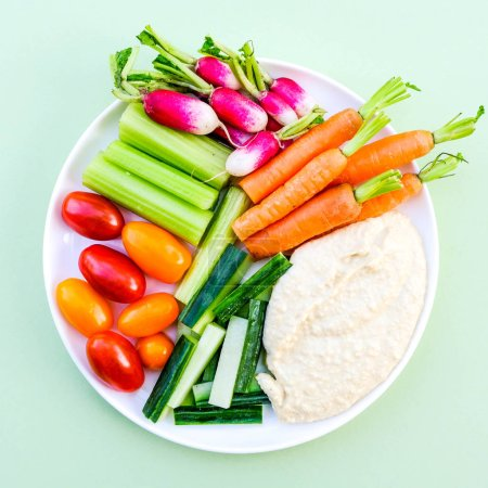 Photo pour Fresh Vegetable Crudite Platter With Hummus and Baby Carrots, Radishes, Cucumber, Celery and Tomatoes - image libre de droit