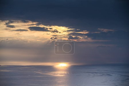 beautiful moody storym sky withclouds hiding the sun and reflection in the sea below