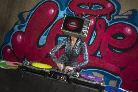 Photo pour Femme avec Tv tête jouant de la musique avec les lèvres à l'écran devant le mot amour graffiti peint sur le mur - image libre de droit