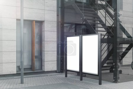 Two blank outdoor banner stands next to bright modern building, 3d rendering.
