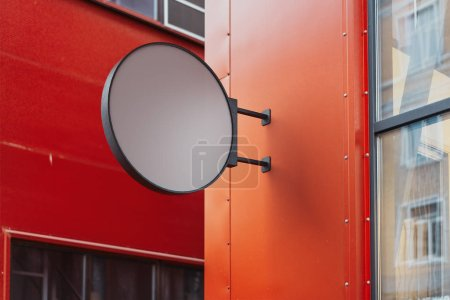 Blank round store signboard. Empty shop lightbox on the red wall. 3d rendering.