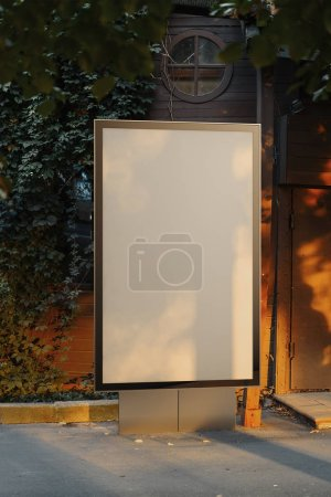 Photo for Blank canvas outdoor banner stand at park. Empty outdoor billboard next to green trees and bushes. 3d rendering. - Royalty Free Image