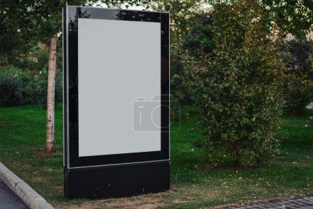 Photo pour Bannière extérieure en toile vierge au parc. Panneau d'affichage extérieur vide à côté des arbres verts et des buissons . - image libre de droit