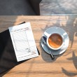 Close up of cheque and coffee cup on wooden table ...