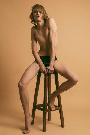 Photo pour Muscle blond beau modèle masculin dépouillé avec des cheveux longs portrait en sous-vêtements noirs sur fond de police isolé beige - image libre de droit