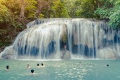 KANCHANABURI THAILAND - NOVEMBER 16 : Many tourists stand in waterfall and taking a shower at Erawan Waterfall