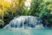 KANCHANABURI THAILAND - NOVEMBER 16 : Many tourists stand in waterfall and taking a shower at Erawan Waterfall