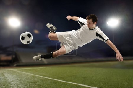 Photo for Soccer player jumping and kicking the ball inside a stadium at night - Royalty Free Image