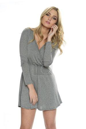 Photo pour Jeune femme blonde tendue portant une robe grise isolée sur un fond blanc - image libre de droit