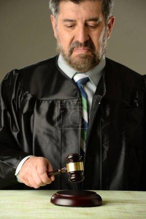 Photo pour Juge tenant un marteau faisant un verdict sur un fond gris - image libre de droit