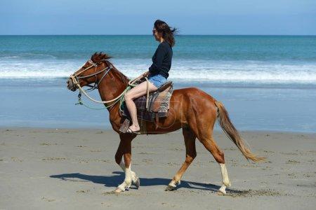 Foto de Mujer montando a caballo por la orilla del océano en un hermoso día soleado - Imagen libre de derechos
