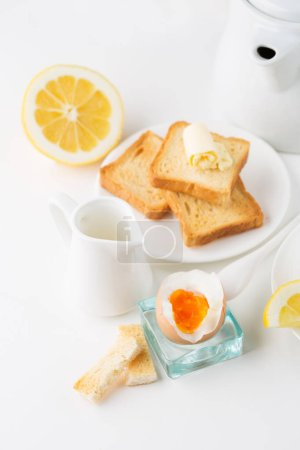 Photo for Breakfast table with soft boiled egg, crispy toasts and cup tea on whiite background, selective focus - Royalty Free Image