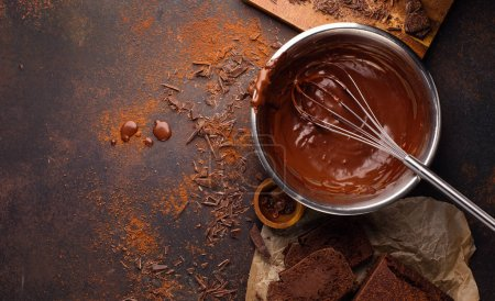 Photo for Homemade delicious chocolate cream in bowl with whisk and cake on dark wooden table, top view - Royalty Free Image