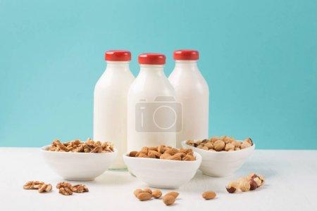 Foto de Leche de nuez alternativa vegana fresca en botellas de vidrio sobre fondo azul y blanco. Concepto de alimentos vegetales saludables - Imagen libre de derechos