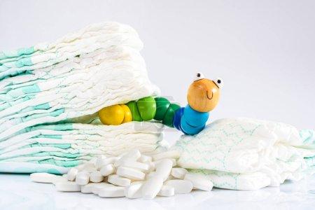 Photo pour Enterobiasis est une infection des vers, Enterobius vermicularis ou vers de pin, qui affecte les enfants et les bébés. Un ver jouet avec des couches et des pilules . - image libre de droit