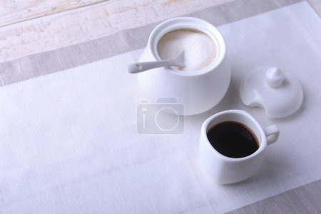 Cup of hot coffee espresso, coffee beans, jug of m...