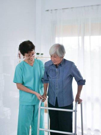 Photo pour Infirmière, aider les personnes âgées femme utilisant Walking Frame. - image libre de droit