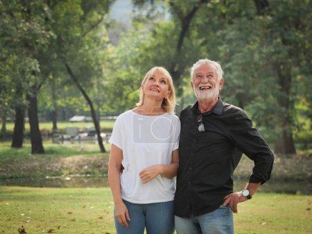 Photo pour Deux retraités heureux L'homme et la femme marchent et parlent dans le parc - image libre de droit