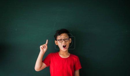 Photo pour Asiatique garçon avec livre sur tableau noir fond éducation école salle de classe concept - image libre de droit