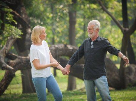 Photo pour Deux retraite seniors heureux homme et femme sont marcher et de parler dans le parc - image libre de droit