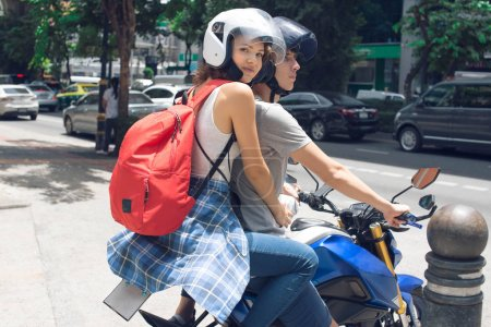 Young woman and man on the bike (city)