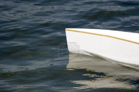 White canoe, kajak and rowing on lake water.