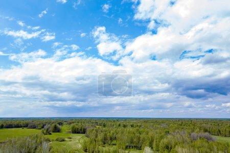 Luftaufnahme einer Landschaft mit grünen Wiesen und Wäldern unter freiem Himmel