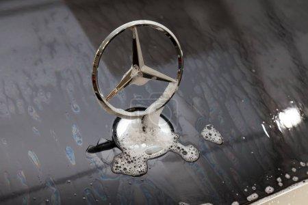Photo pour Novossibirsk, Russie - 19.07.2019 : Gros plan sur l'emblème d'un constructeur automobile Mercedes Benz sur le capot d'une voiture noire pendant le lavage et le nettoyage dans un atelier de détail avec de la mousse et de l'eau dans du savon - image libre de droit