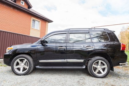 Photo for Novosibirsk, Russia - 09.26.2020: Side view of Toyota Land Cruiser 200 in black color after cleaning before sale in a sunny day on parking. Japan SUV car. - Royalty Free Image