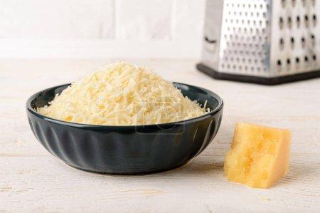 Grated parmesan or grana padano in a ceramic bowl ...