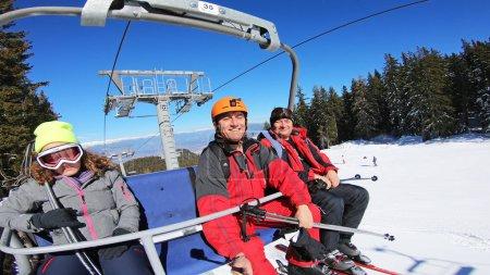 Foto de Turistas tomando selfie en telesilla subiendo a una estación de esquí en las laderas de la cumbre de la montaña en Bansko - Imagen libre de derechos